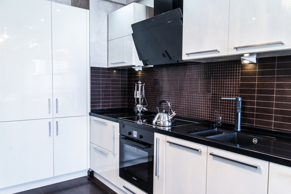 Кухня с белыми шкафчиками и темной столешицей
