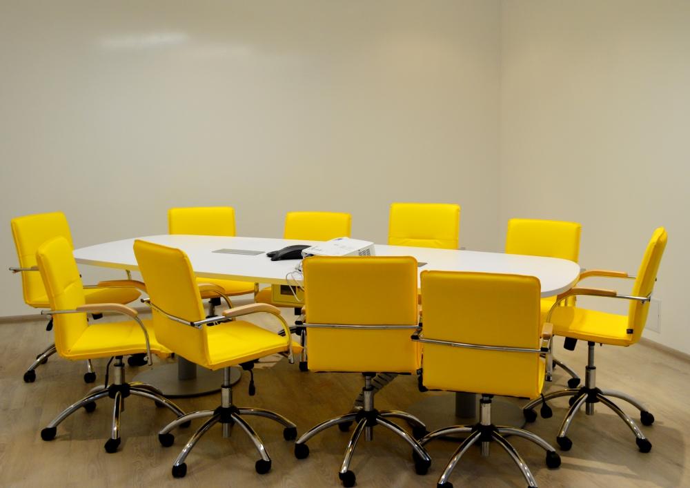 Белый стол и яркие желтые стулья в переговорной комнате